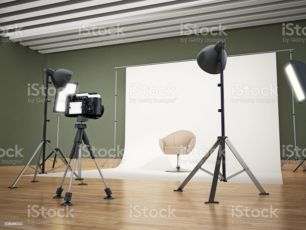 Photographic studio with camera standing on the tripod and lighting...