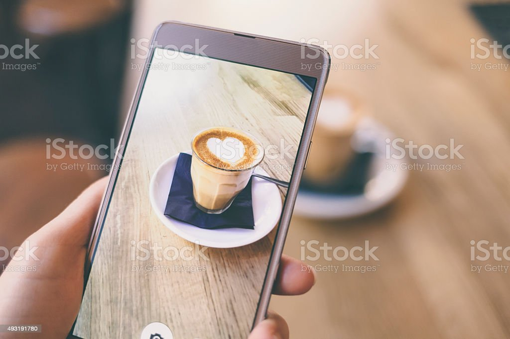 Photographing coffee with smart phone stock photo