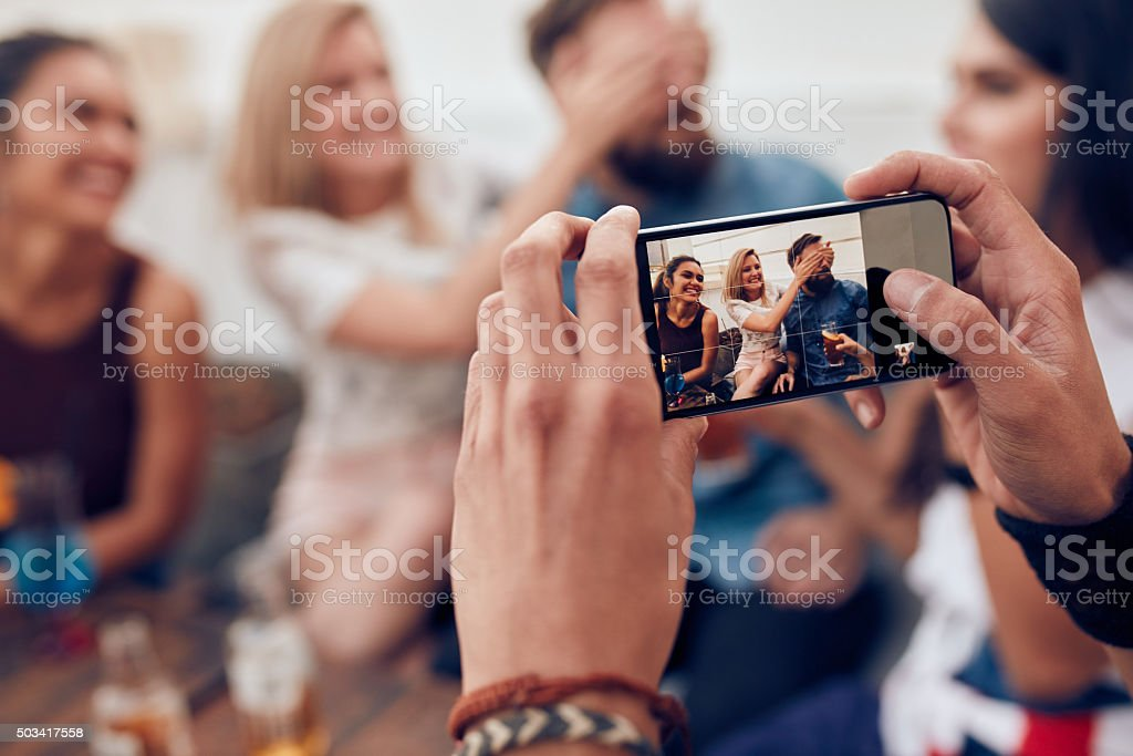 Photographing friends at party with mobile phone stock photo