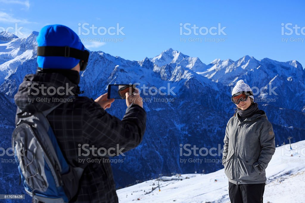 Photographing  Snow skier  best friends  teens boy and girl enjoying stock photo