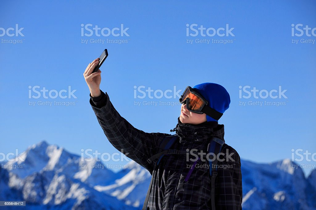 Photographing  Snow skier teenage boy taking selfie photo  Alps mountain stock photo