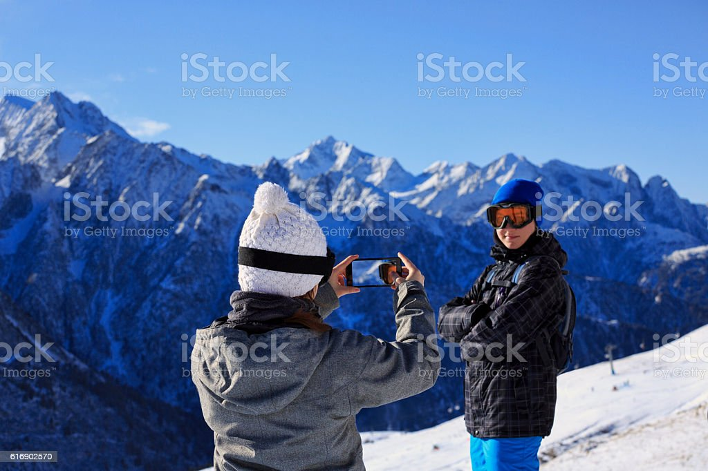 Photographing  Snow skier teenage couple taking  photo  Alps mountain landscape stock photo
