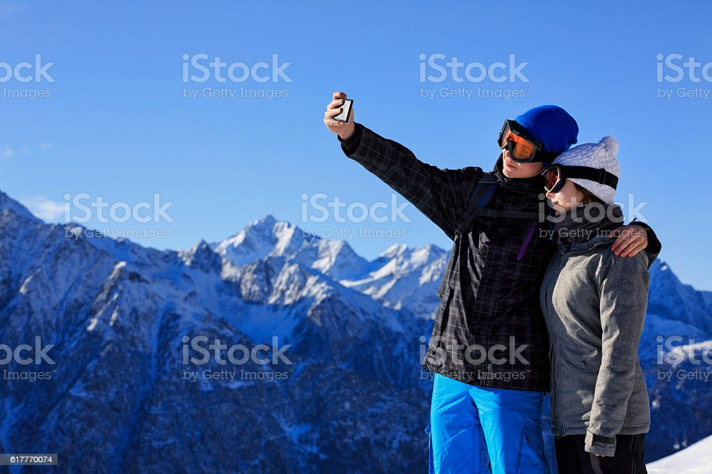 Photographing  Snow skier teenage couple taking selfie photo  Alps mountain stock photo