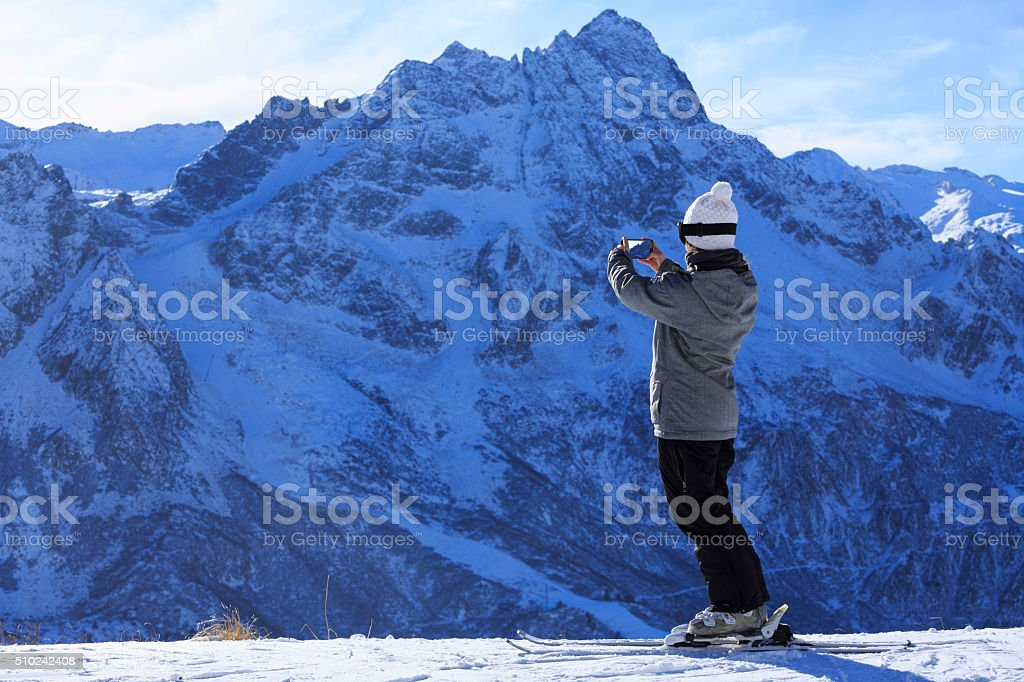 Photographing  Snow skier young woman taking landscape photo  Alps mountain stock photo