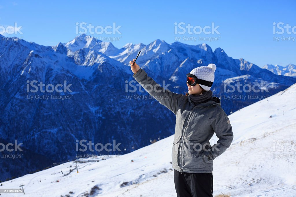 Photographing  Snow skier young woman taking selfie photo  Alps mountain stock photo