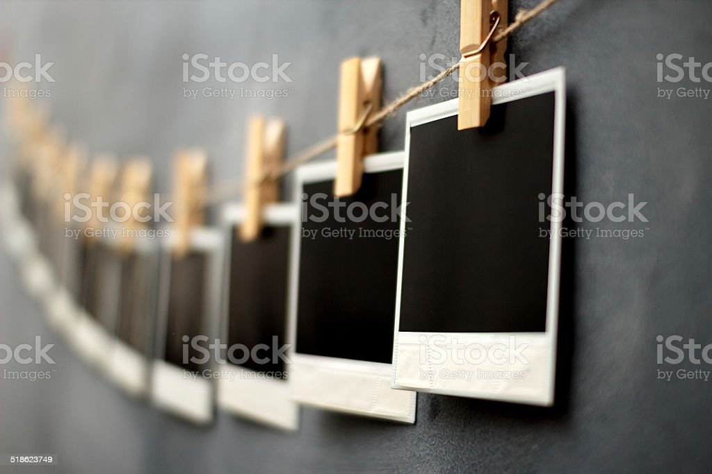 Photography paper with instant photo frames attached to rope wit stock photo
