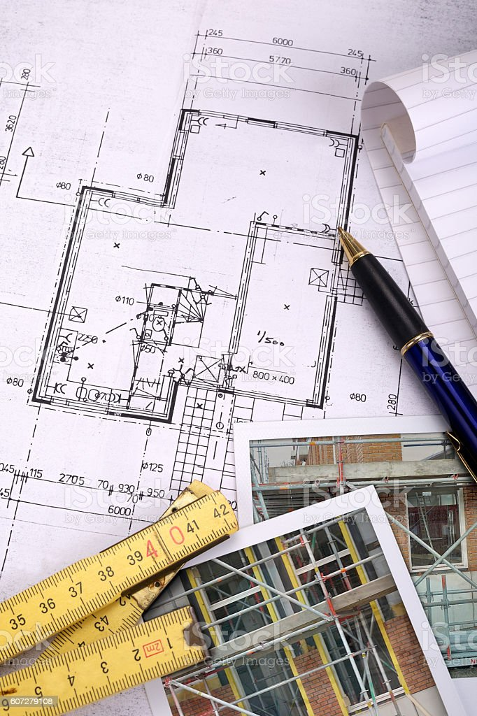 Photos and folding ruler on top of a blueprint stock photo