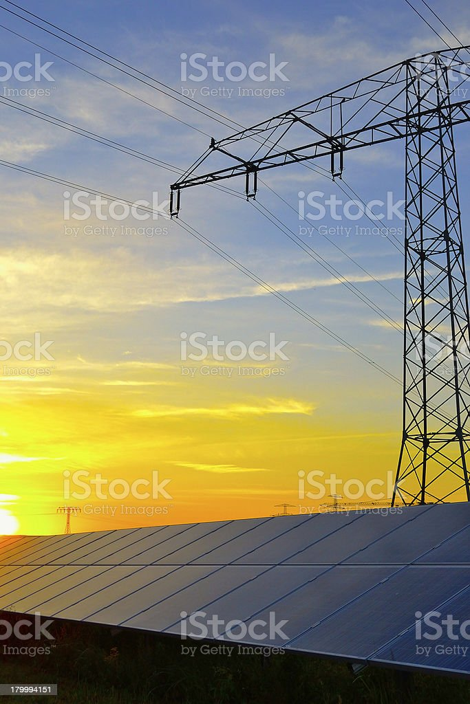 Photovoltaic panel's and electricity pylon at sunset royalty-free stock photo