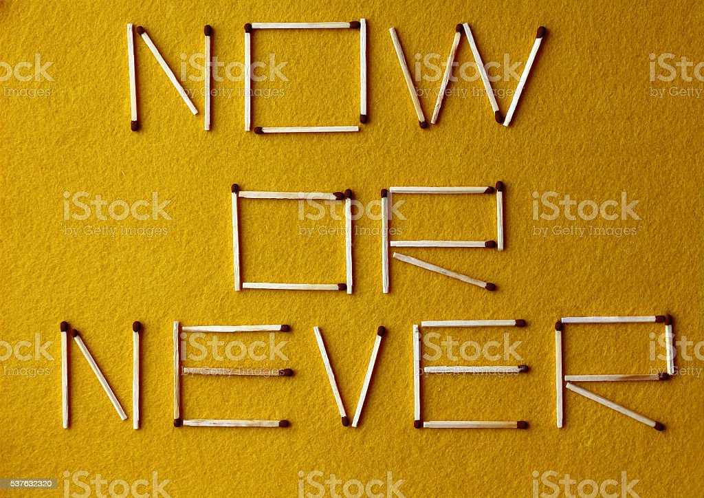 phrase 'now or never' laid matches on yellow felt background, stock photo