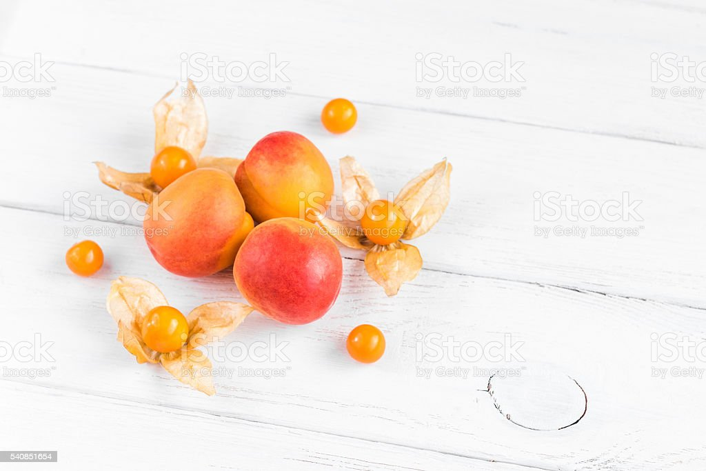 physalis and apricot on white wooden background stock photo