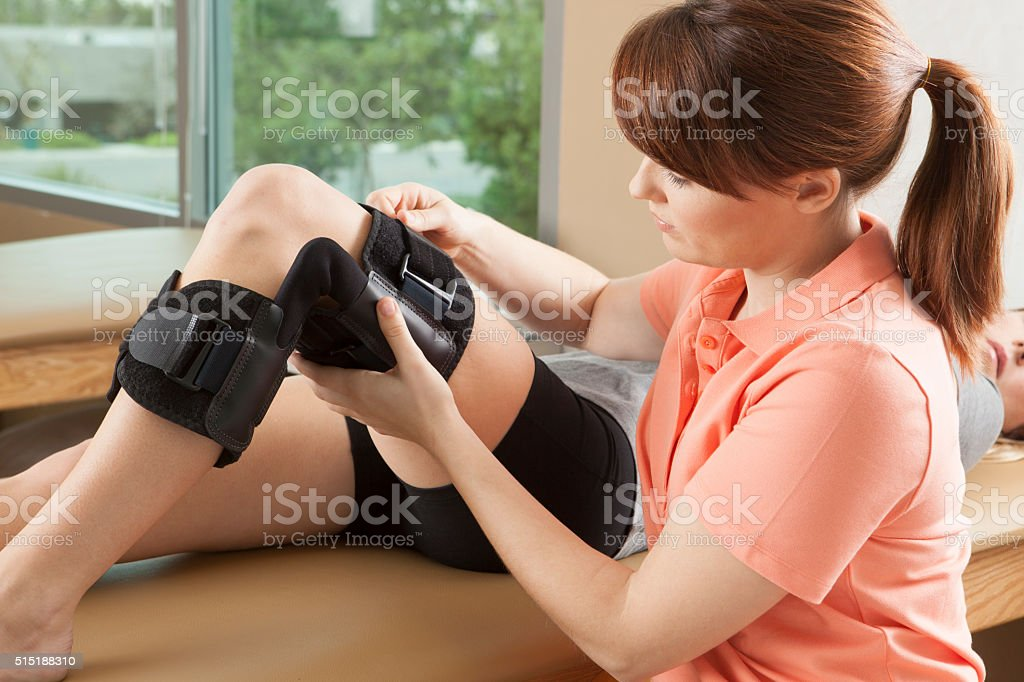Physical therapist adjusting a knee brace on female patient stock photo
