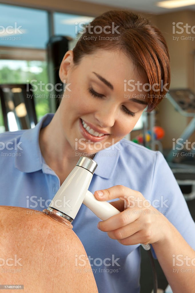 Physical therapist administering ultrasound on a man's shoulder. royalty-free stock photo