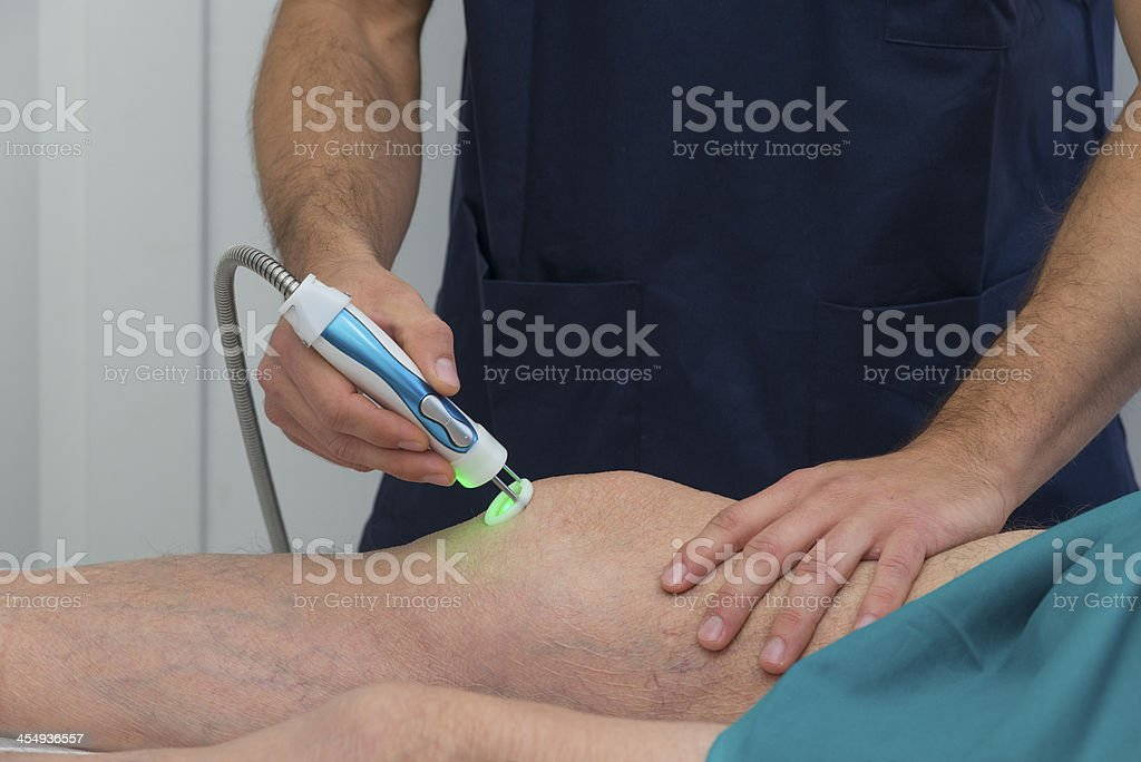 Physical therapist aiding a patient's knee in rehabilitation stock photo