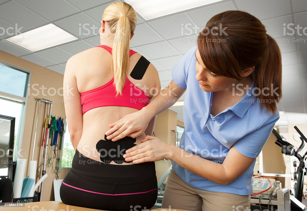 Physical therapist applying kinesio tape to patient's lower back stock photo