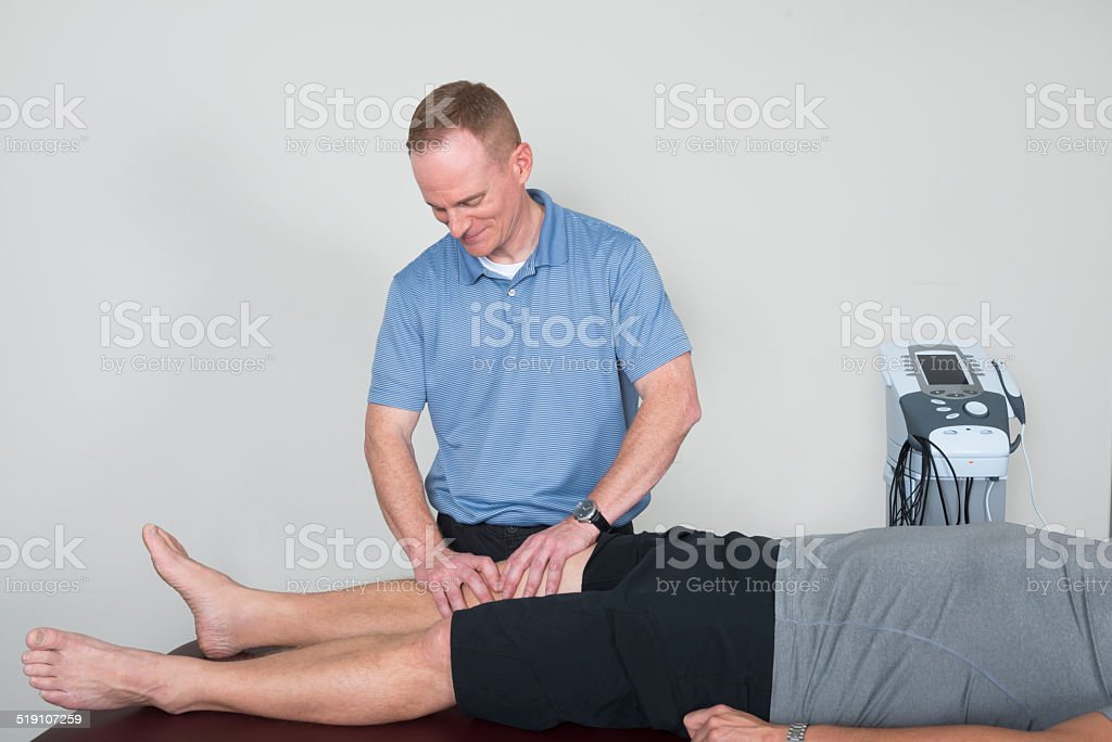 Physical Therapist Assessing Patient's Knee stock photo