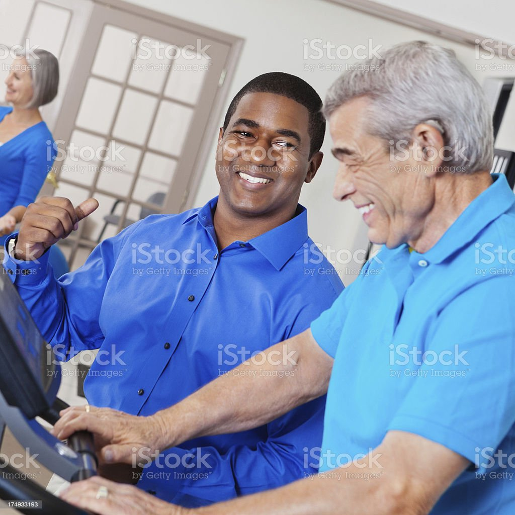 Physical therapist assisting senior patient in rehabilitation gym royalty-free stock photo