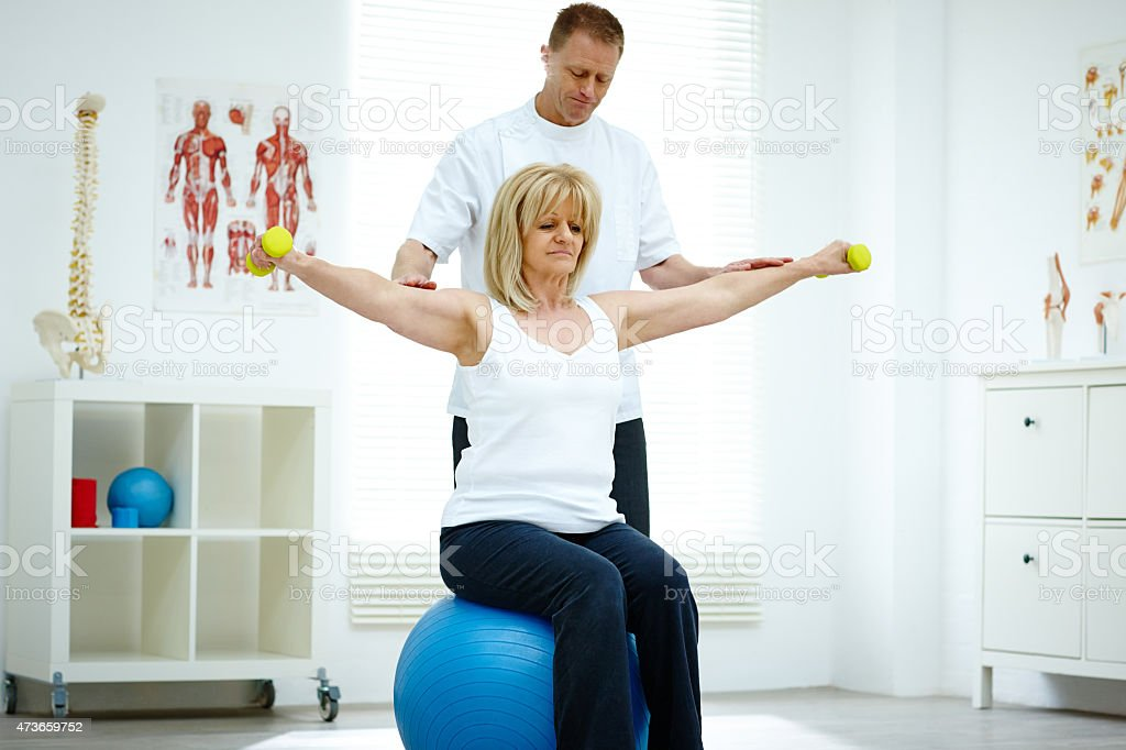 Physical therapist assisting senior woman at medical gym stock photo