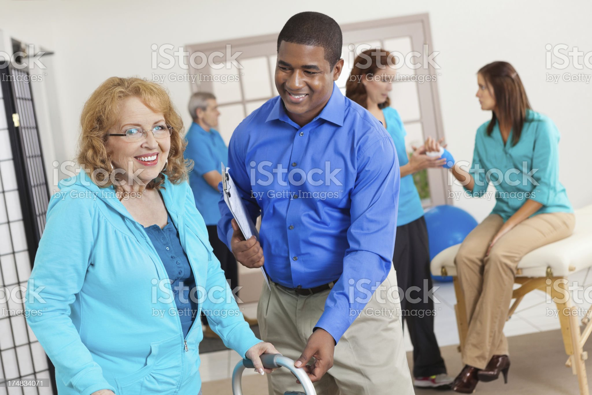 Physical therapist assisting senior woman with walker in clinic royalty-free stock photo