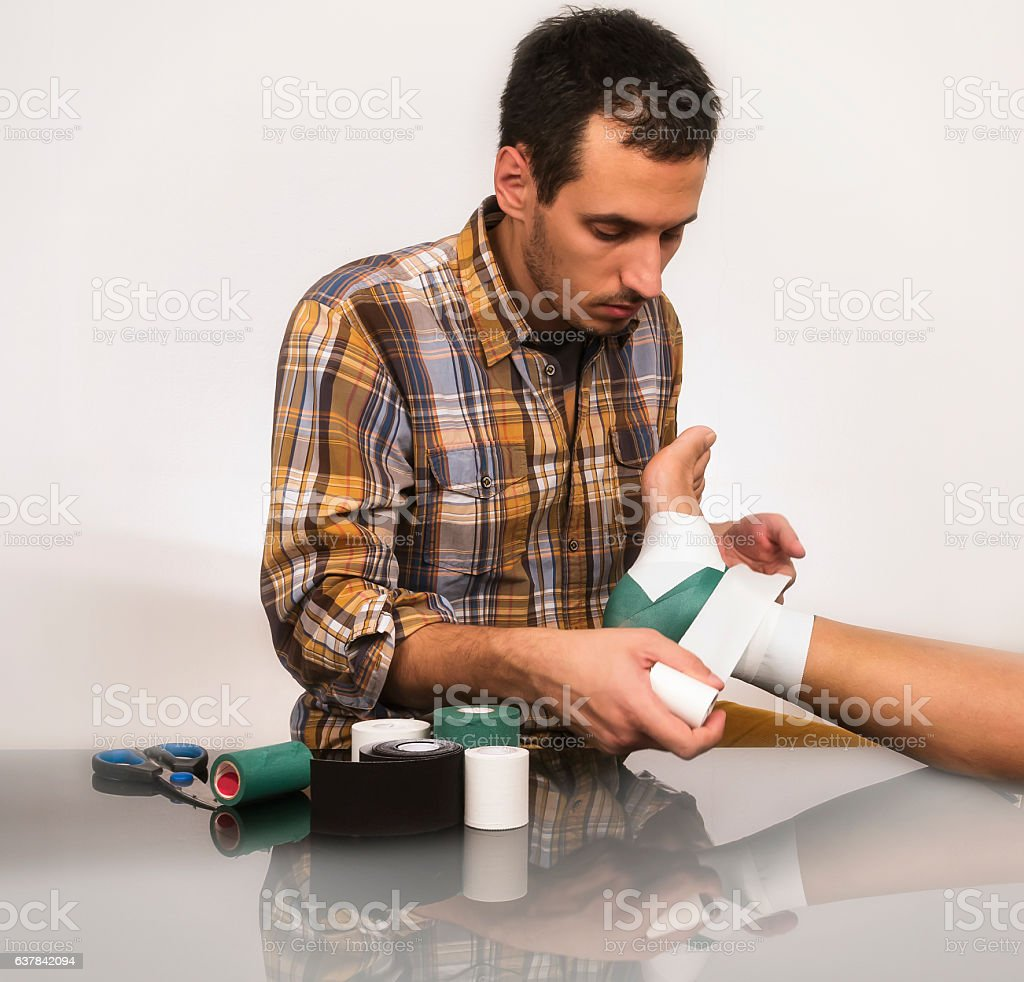 Physical therapist Bandaging Woman Ankle stock photo