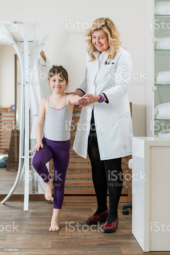 Physical therapist doing medical exam with little boy stock photo
