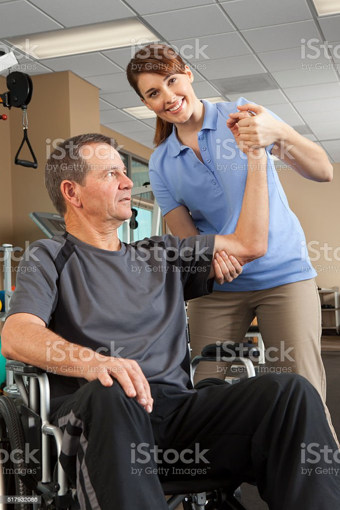Physical Therapist Evaluates Range Of Motion Of Patient In Wheelchair stock photo