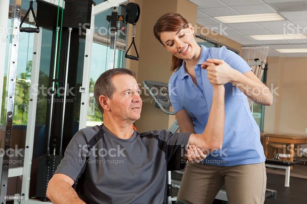Physical therapist evaluating range of motion of patient in wheelchair stock photo