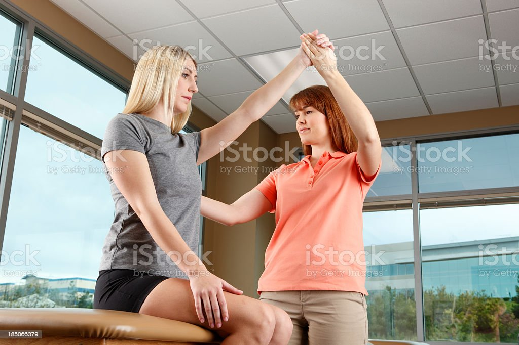 Physical therapist evaluating range of motion of patient's shoulder royalty-free stock photo