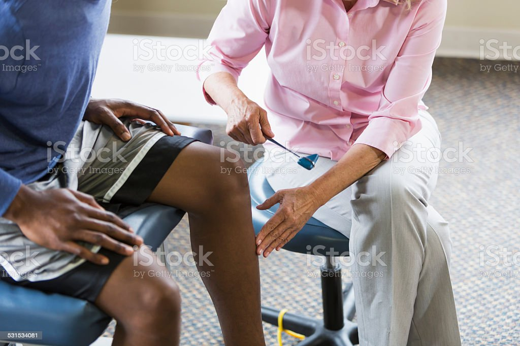 Physical therapist examining patient stock photo
