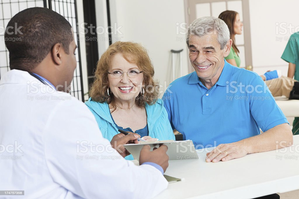 Physical therapist explaining medical results to senior couple royalty-free stock photo