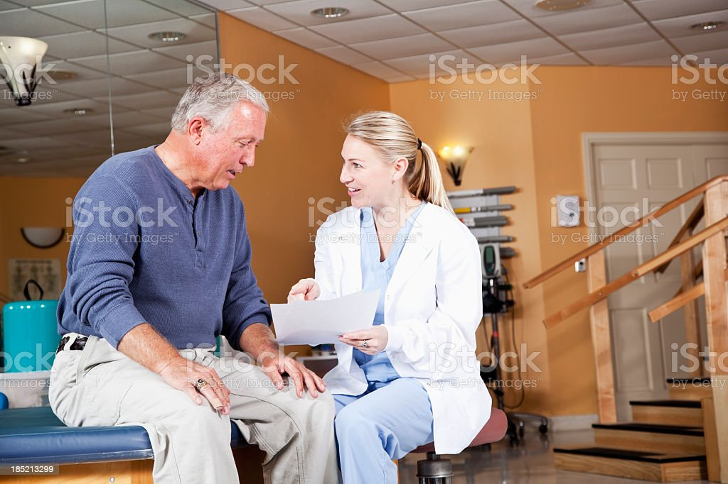 Physical therapist explaining treatment plan to patient stock photo