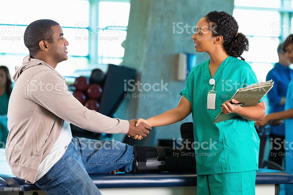 Physical therapist greeting patient in hospital rehab gym stock photo