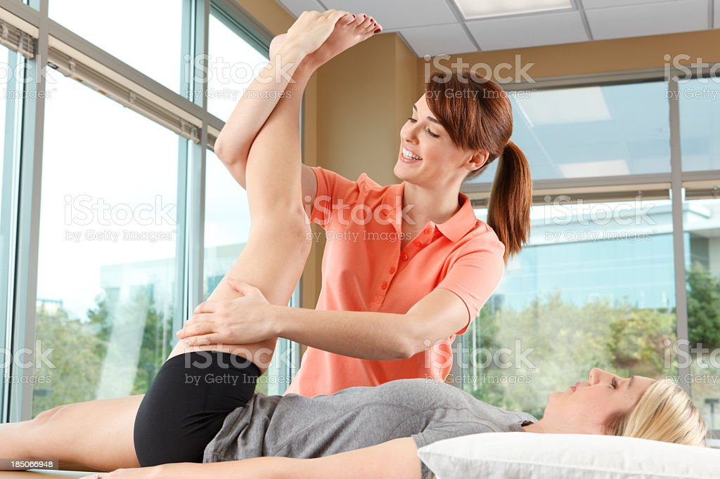 Physical therapist helping a woman stretch her leg royalty-free stock photo