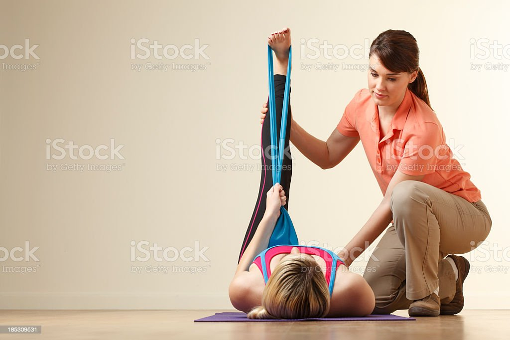 Physical therapist helping a young woman stretch her hamstring royalty-free stock photo