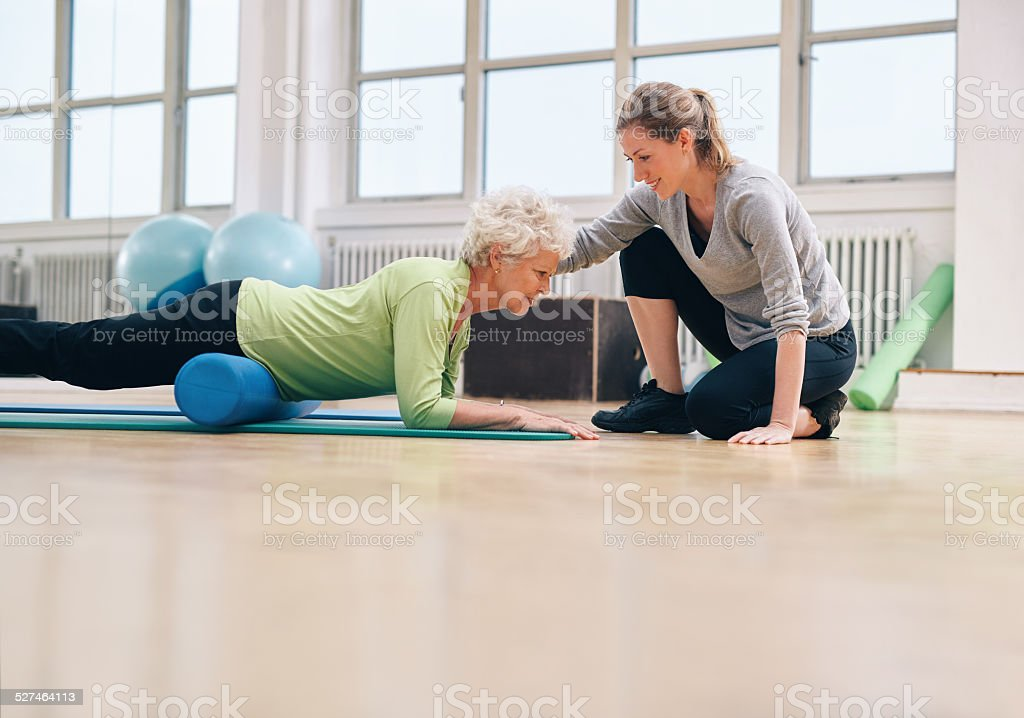 Physical therapist helping elderly woman in her workout stock photo