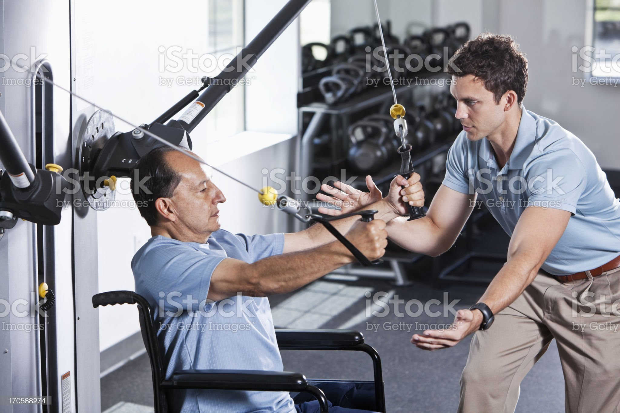 Physical therapist helping patient in wheelchair royalty-free stock photo