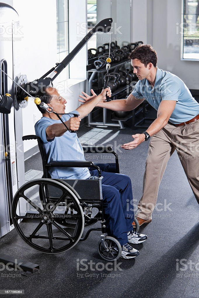 Physical therapist helping patient in wheelchair stock photo