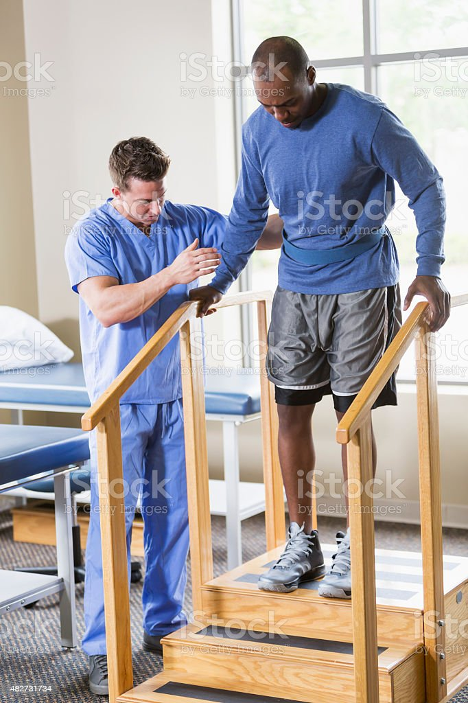 Physical therapist helping patient on stairs stock photo