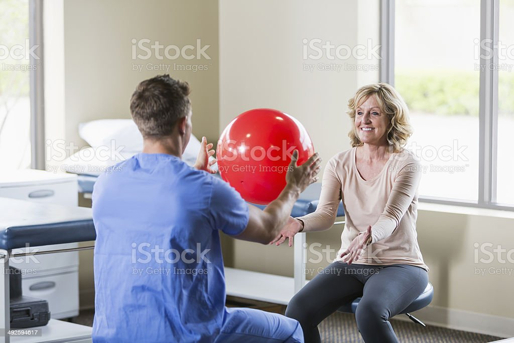 Physical therapist helping patient stock photo