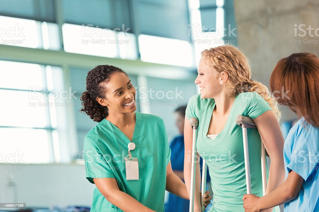 Physical therapist helping teenage patient in rehabilitation hospital stock photo