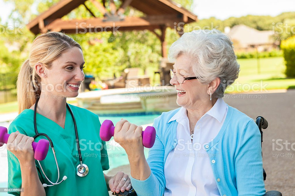 Physical therapist helps senior patient with rehabilitation stock photo