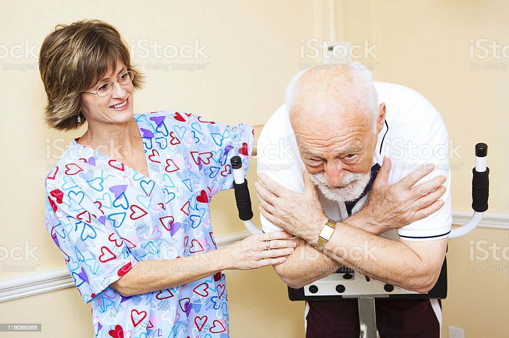 Physical therapist in heart scrubs working with a senior royalty-free stock photo