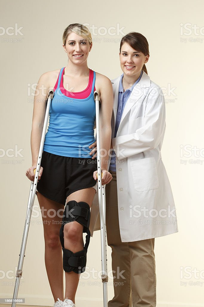 Physical therapist instructing patient on proper use of crutches stock photo