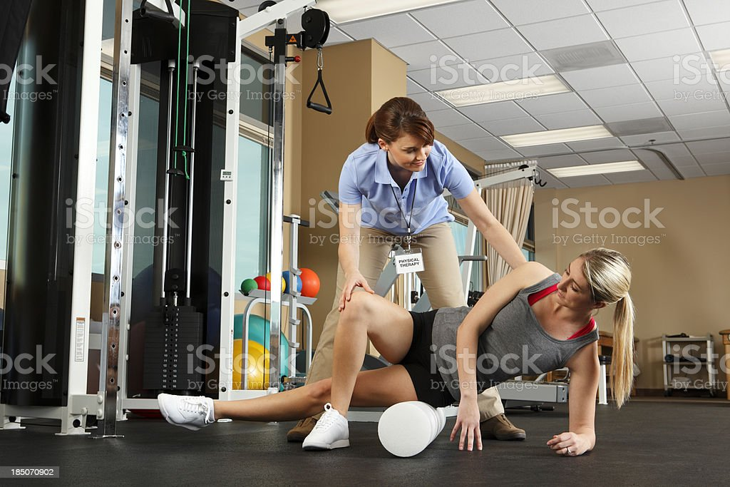 Physical Therapist instructing patient on use of foam roller royalty-free stock photo
