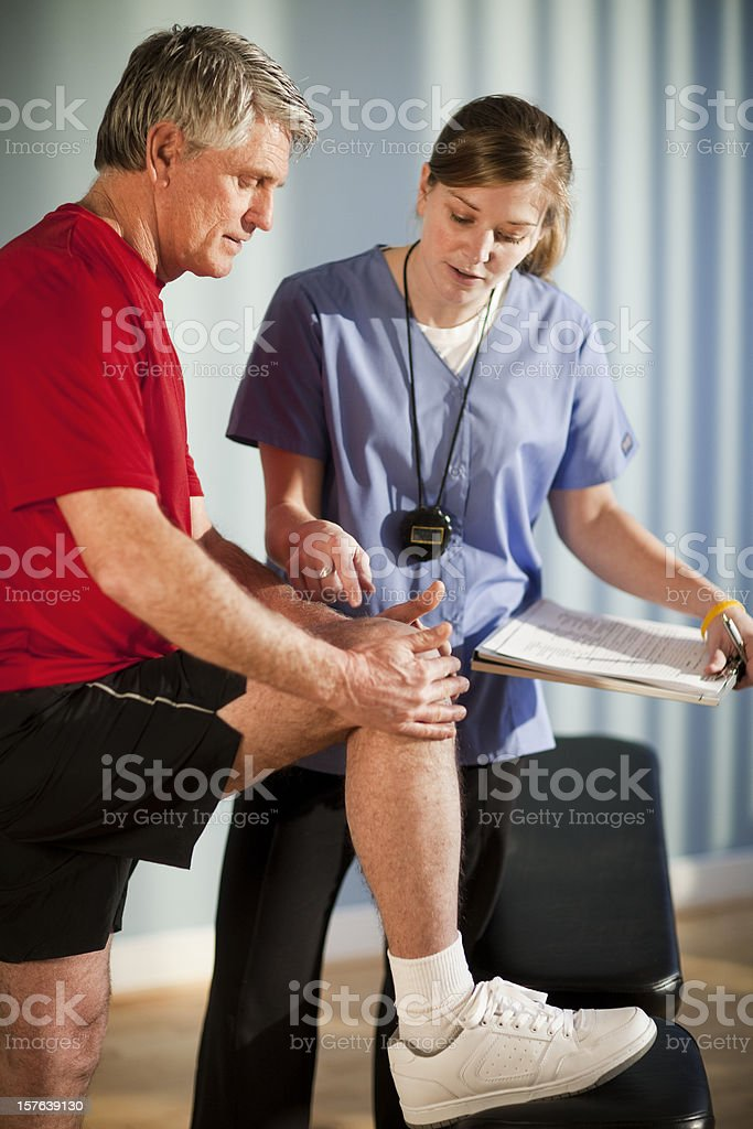 Physical Therapist Looking at Knee Injury royalty-free stock photo