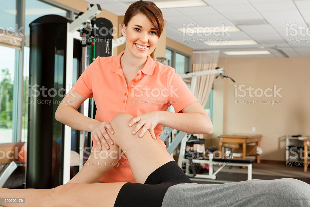 Physical Therapist Manipulates A Young Woman's Leg stock photo