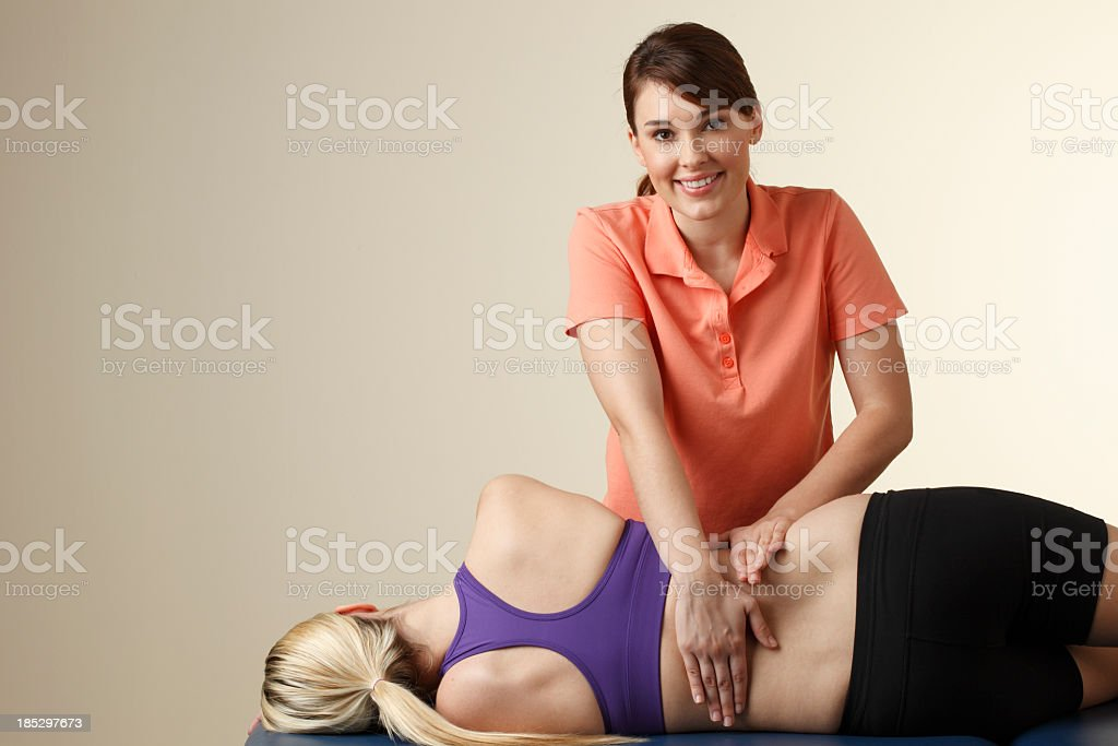 Physical therapist massaging the back of a female patient royalty-free stock photo