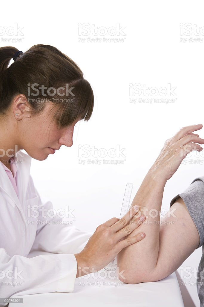 Physical therapist measures the range of motion in an elbow royalty-free stock photo