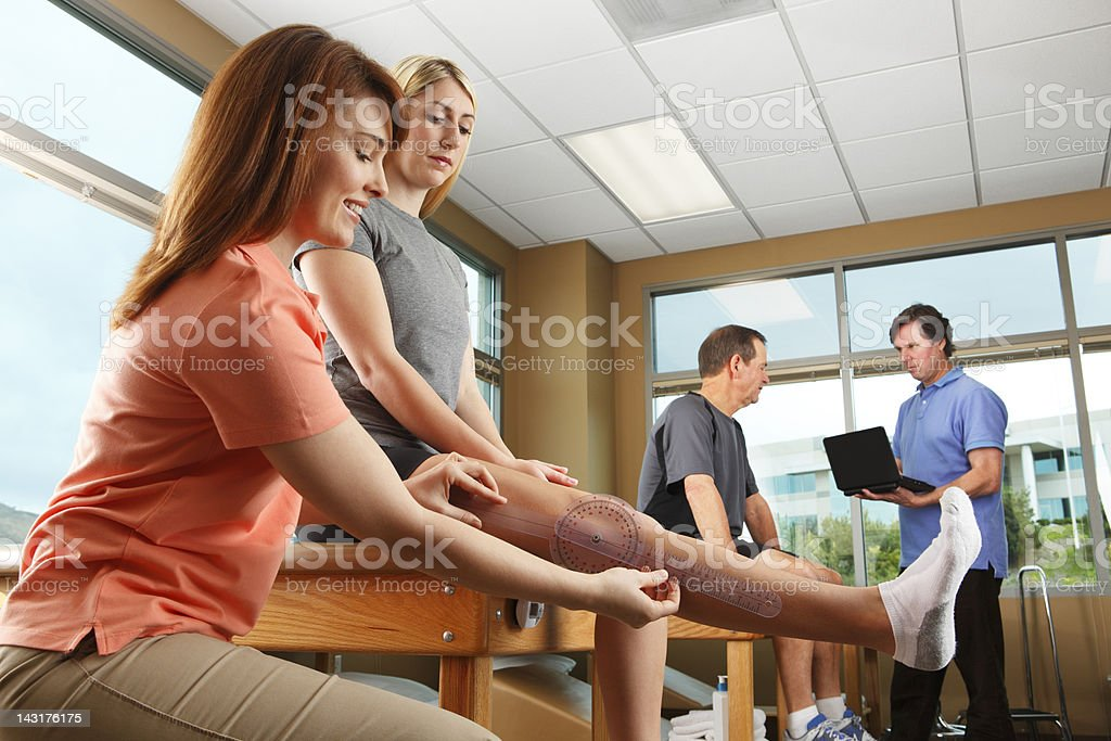 Physical therapist measuring a female patient's knee extension royalty-free stock photo