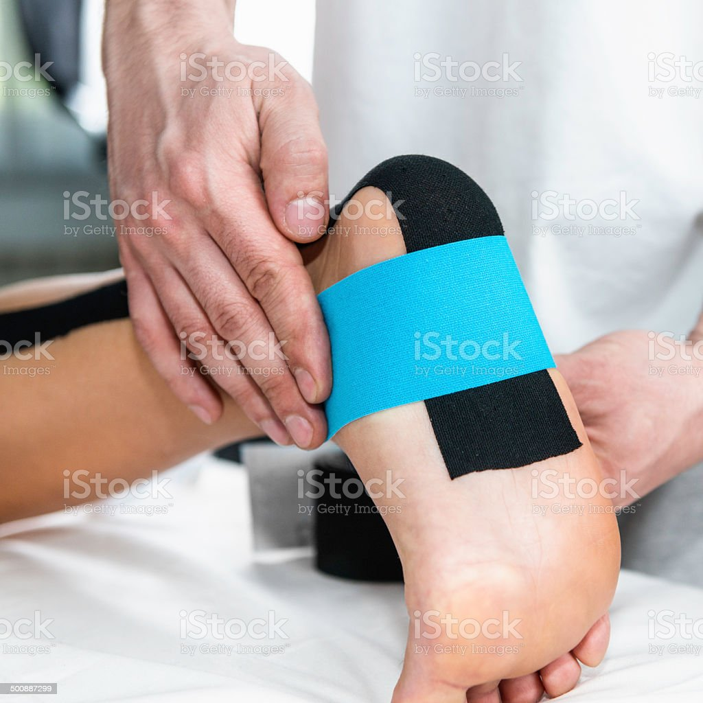 Physical therapist placing taping on patient's foot stock photo