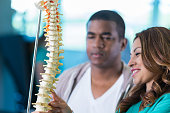 Physical therapist talks with patient about spine injury